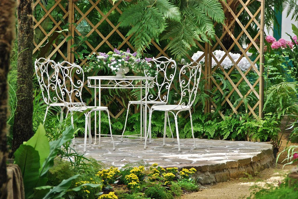 Small garden patio with four white chairs and a table.