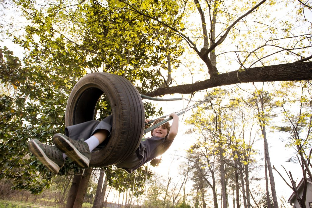 Young boy swinging into a tyre swing in a garden.