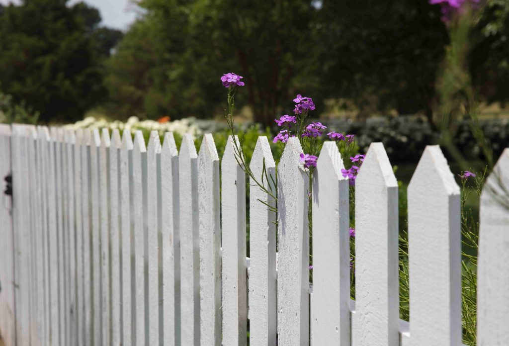 a wide fence in front of a garden