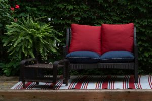 A red sofa and a table in a small garden