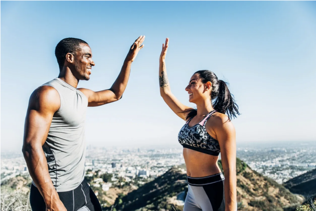 Man and women high fiving after exercising and being happy.