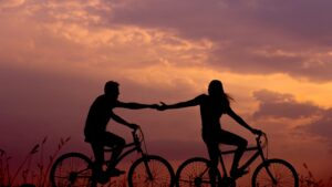 Man and woman couple holding hands and cycling
