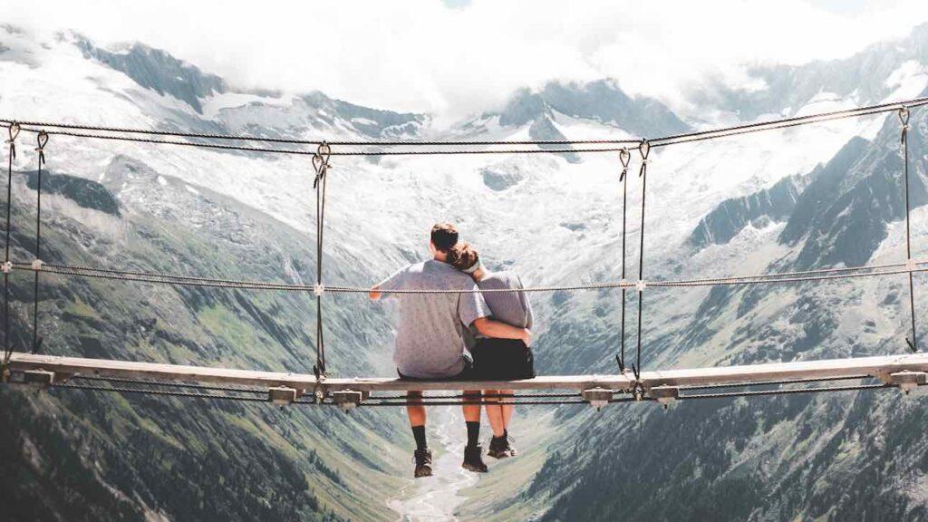Couple sitting on bridge high up