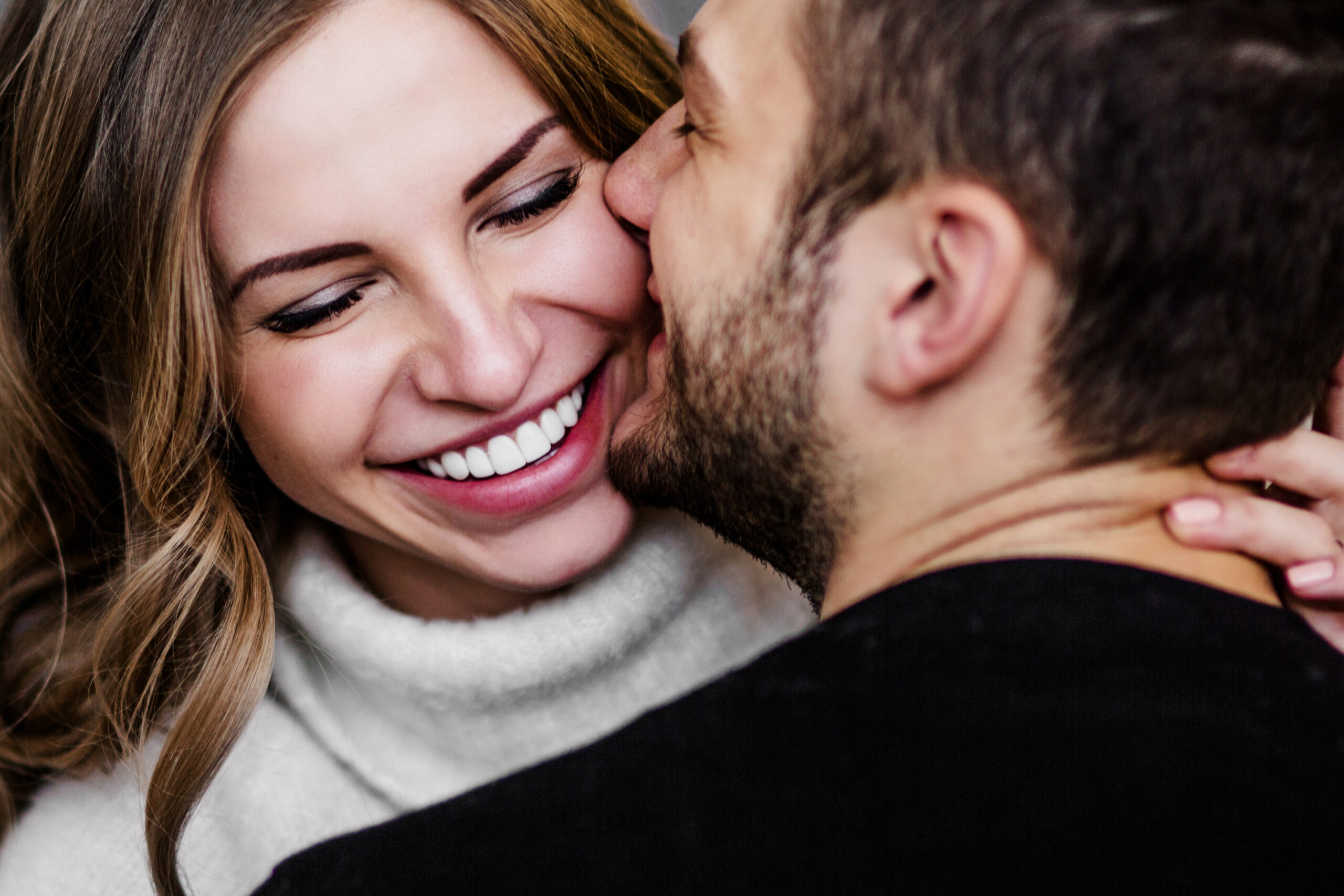 Man and woman smiling and kissing.