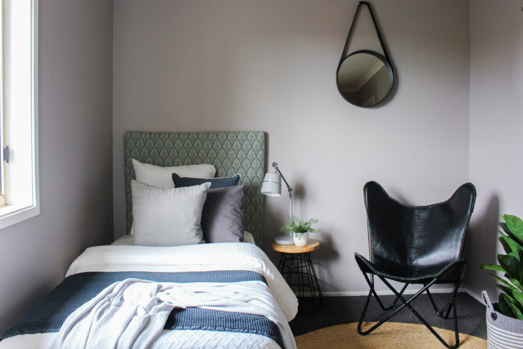 Single bedroom styled with green bedhead, round jute rug and black occasional chair.