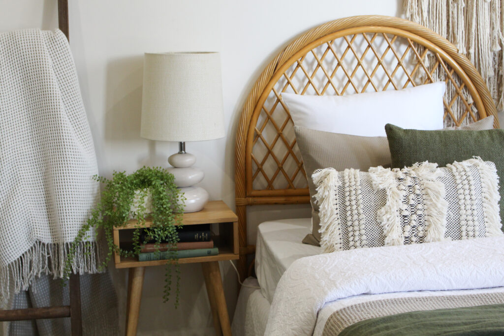 Single bedroom styled with green and white linen, rattan bedhead and bedside plant