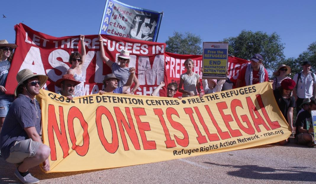 UC RAC members hold banner reading 'No one is illegal' at free the refugees rally.