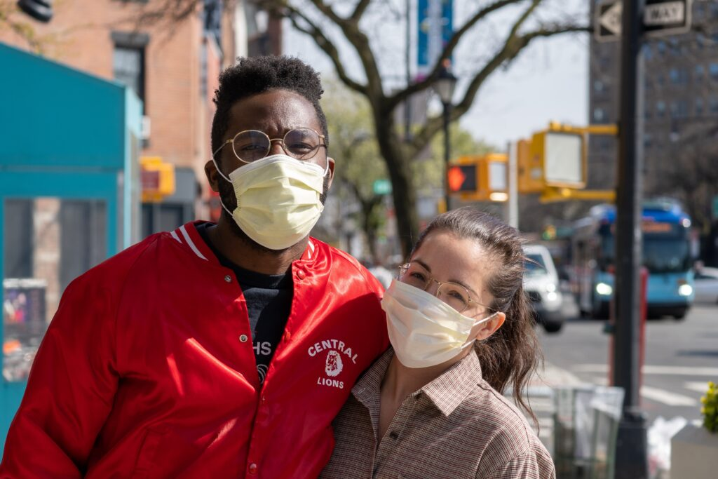 Couple pose for photo while wearing face masks
