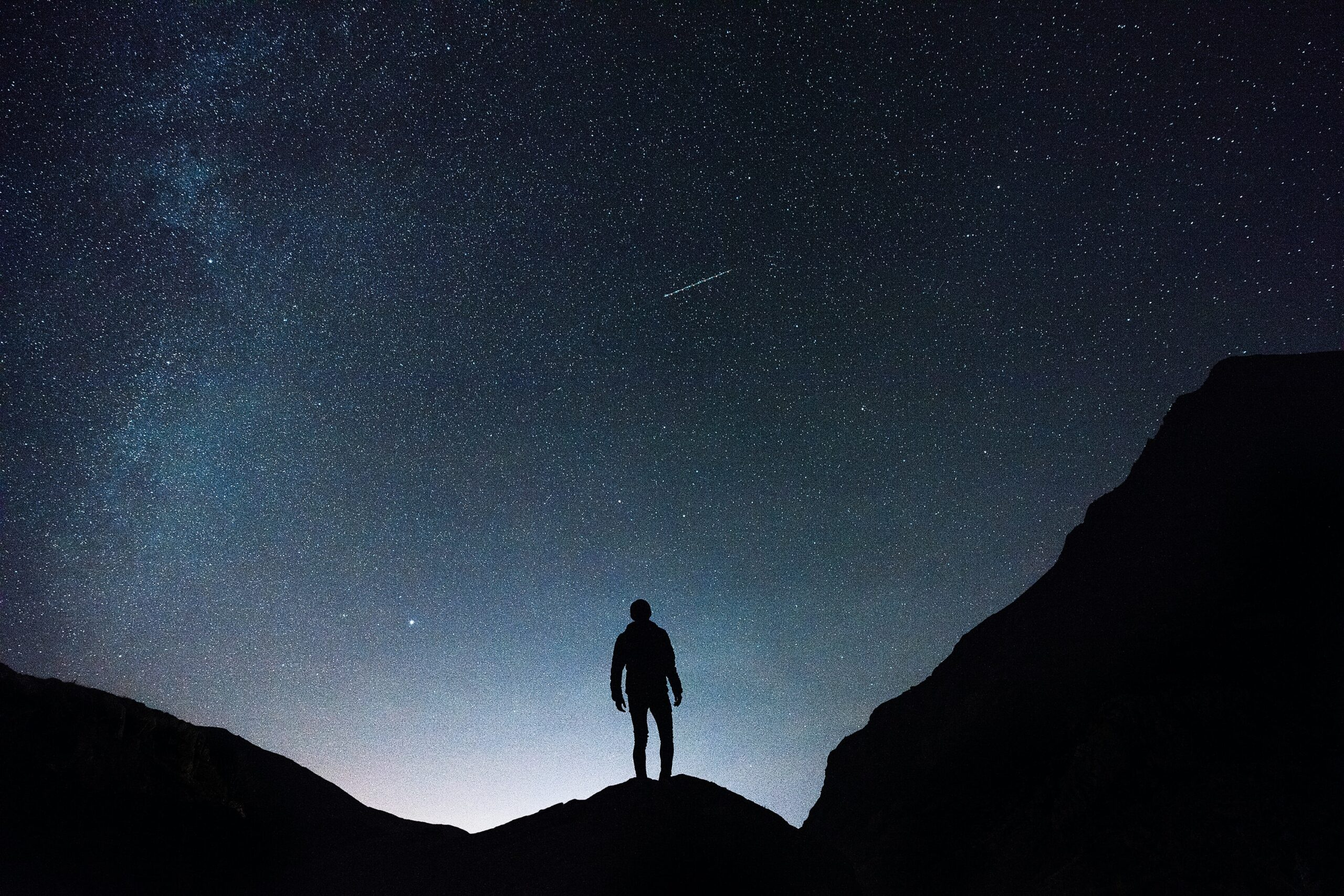 Man stands alone, watching a shooting star.