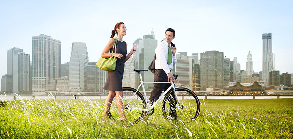 man and woman walking in a field with a bike with a city in the background