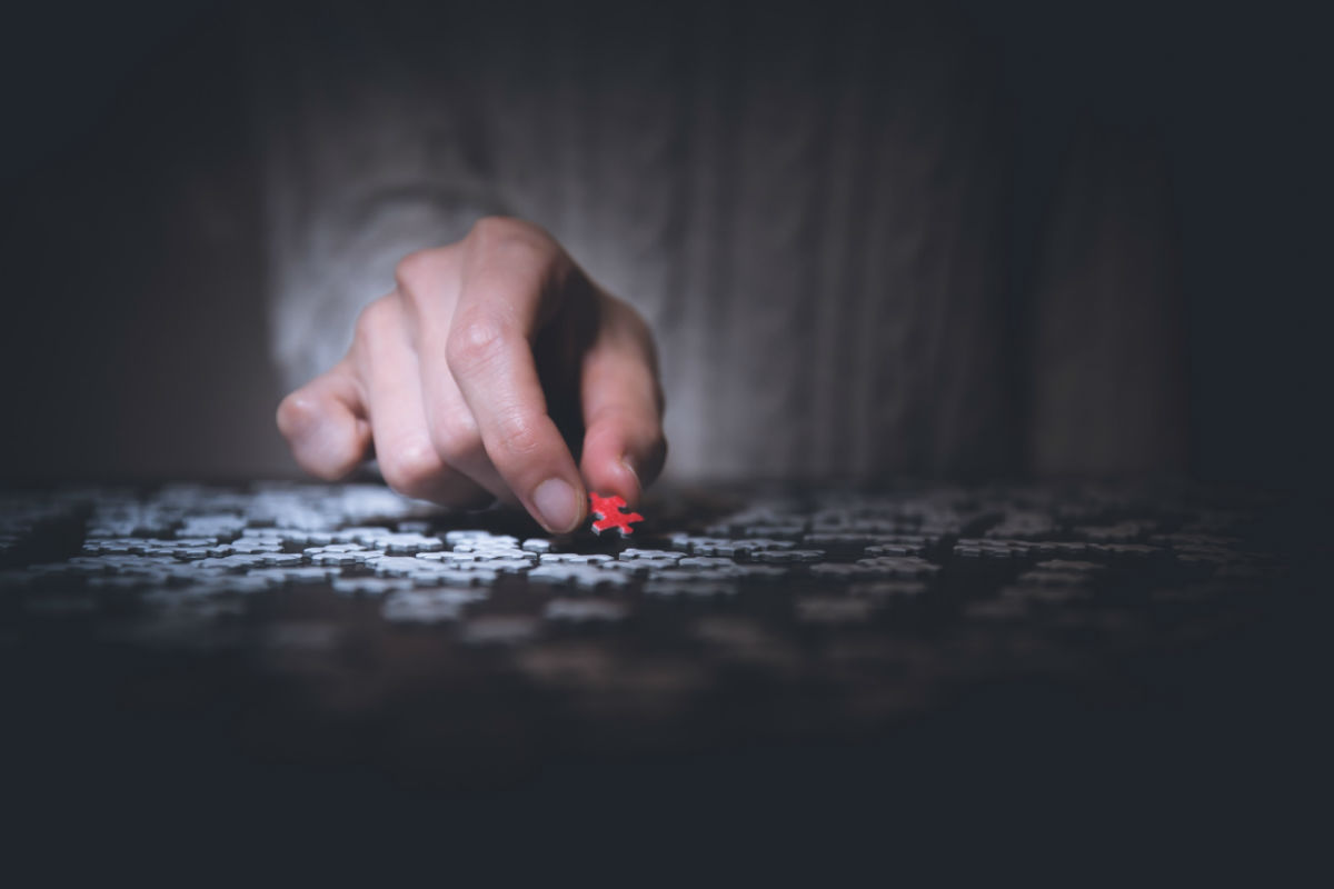 Man holding red puzzle piece