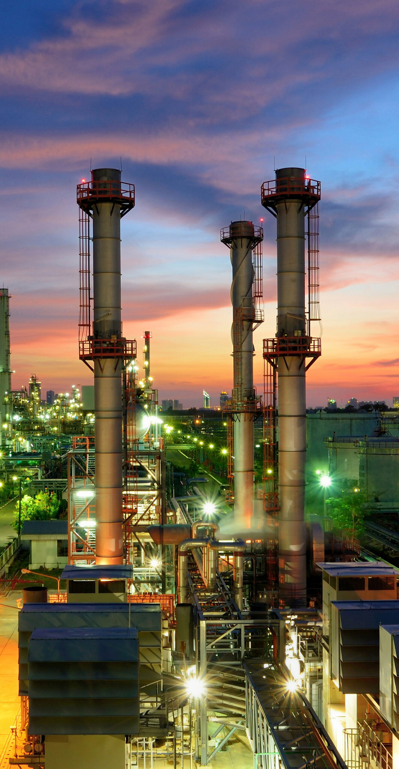 Oil refinery plant at sunset, The night view of petroleum and petrochemical factory with distillation column, drum and pipeline. Gas, diesel and chemical business industry is important for economy.