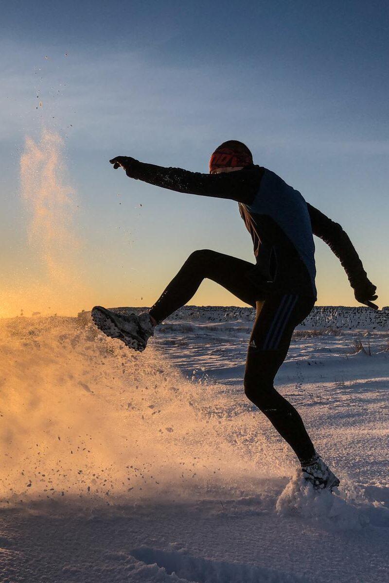 Kicking snow at sunrise