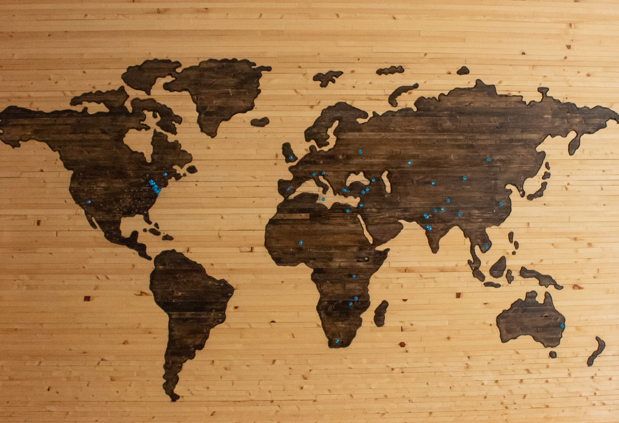 wooden world map with pins in it