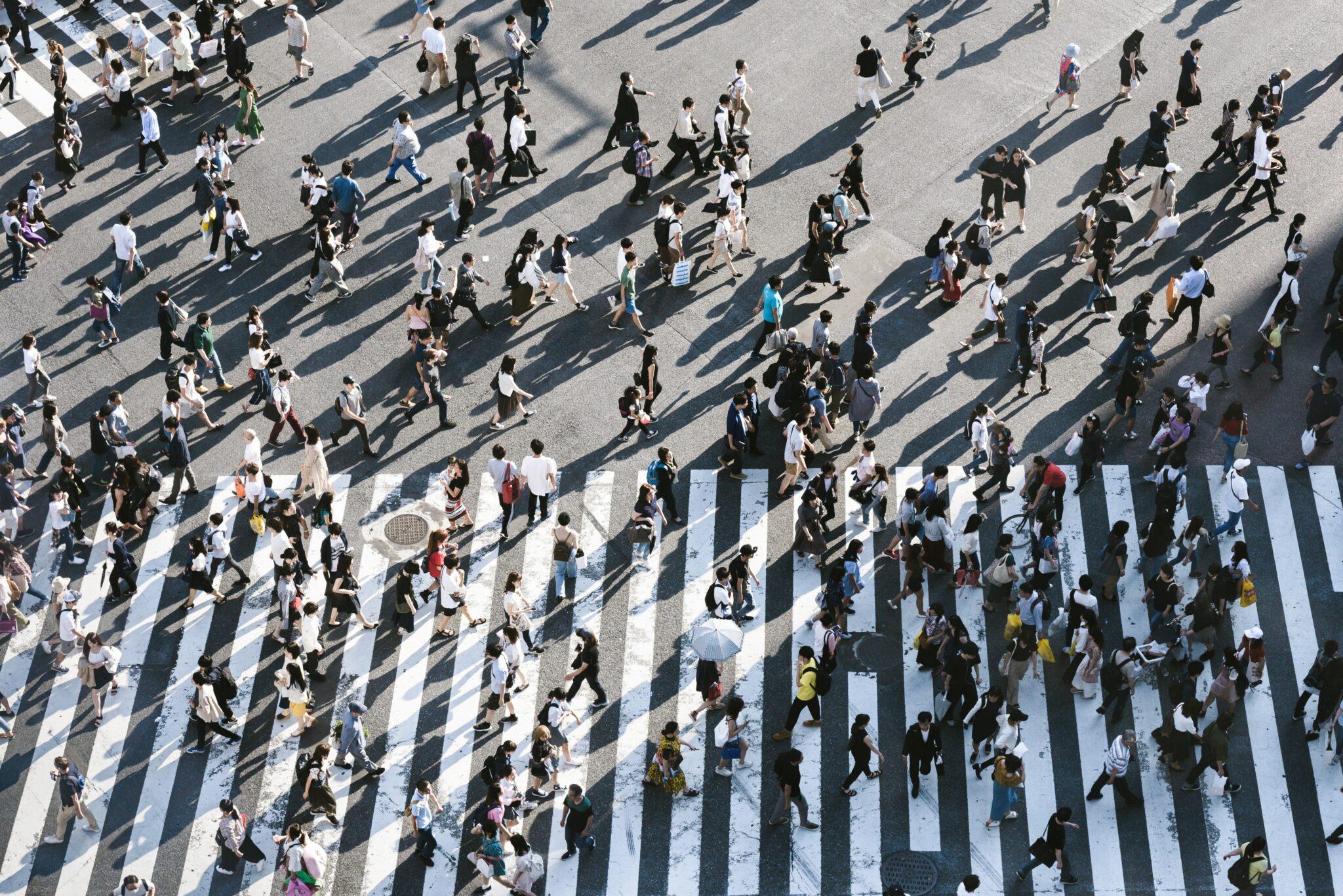 lots of people walking across zebra crossing