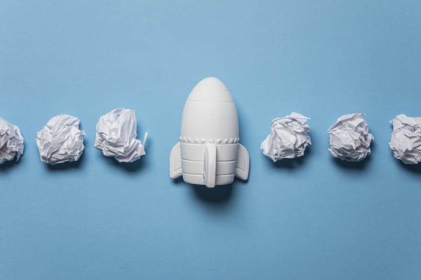Business startup concept. Rocket taking off with crumpled paper trail