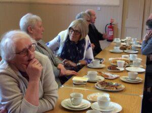 people talking, drinking tea and eating cake