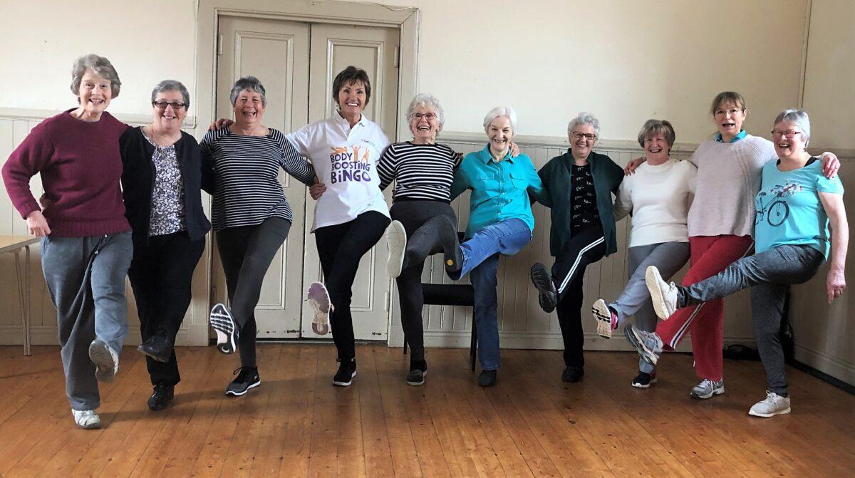 exercise group doing high kicks