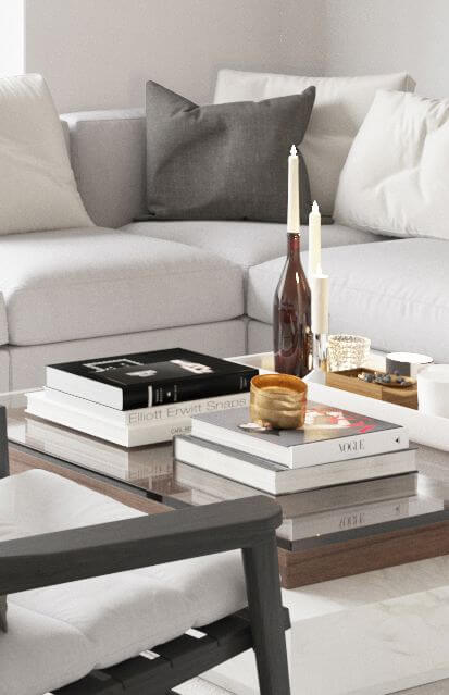 A Close up of the living room details at The Promenade shows high end accesories , including coffe table art books & lighted candles.
