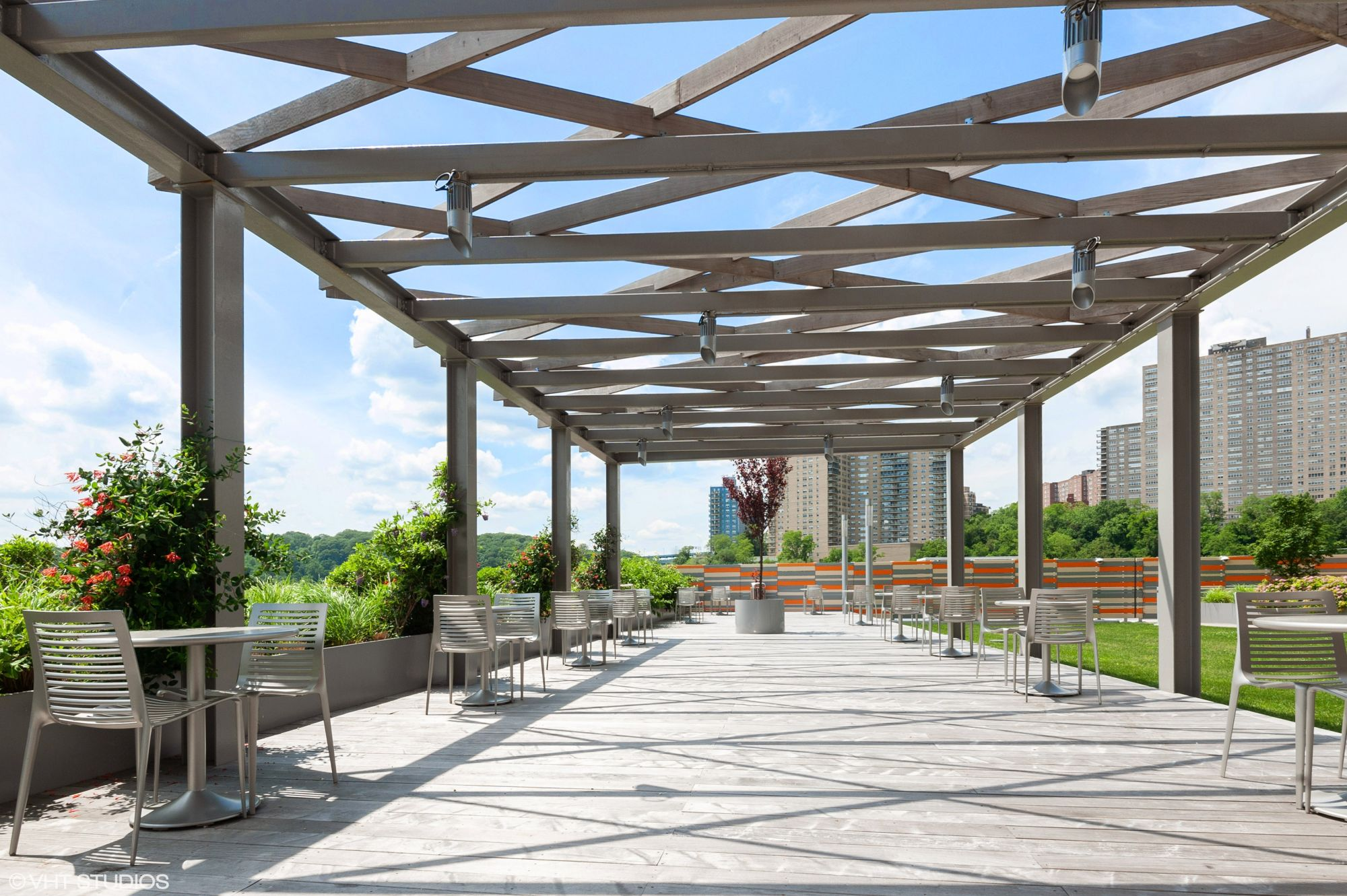 The Landscaped Garden Terrace at The Promenade, 150 west 225th street, is Furnished with modern tables & chairs under a pergola.
