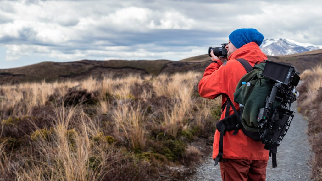 A photographer clicking landscapes while trekking.