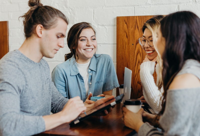four young people meeting in a cafe and having a discussion sitting at a table