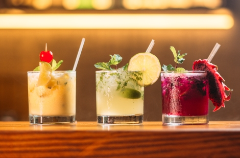 three colourful cocktail drinks sitting on a wooden bar