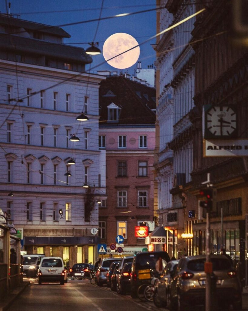 A stunning image captured in Vienna, Austria. The bright supermoon peeps through the  buildings in a busy street.