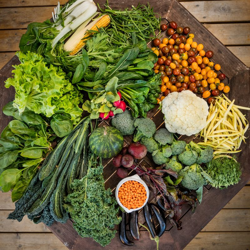 Different green vegetables lying on a tabletop