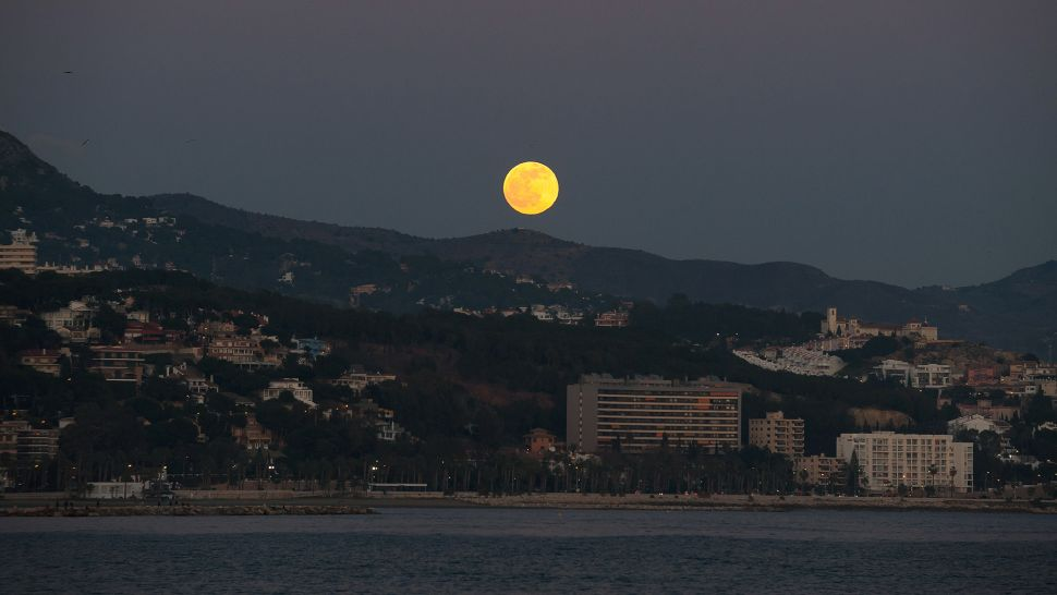 A Full Wolf Moon can be seen rising over the horizon at the beach in Malaga, Spain.