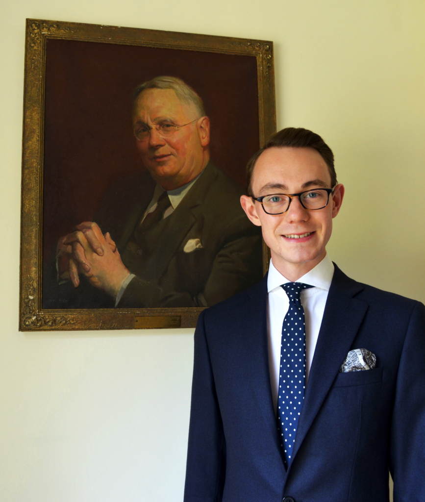 Nicholas Bowman Scargill, in front of a portrait of Amos Reginald Fear, 3rd MD of the Company.