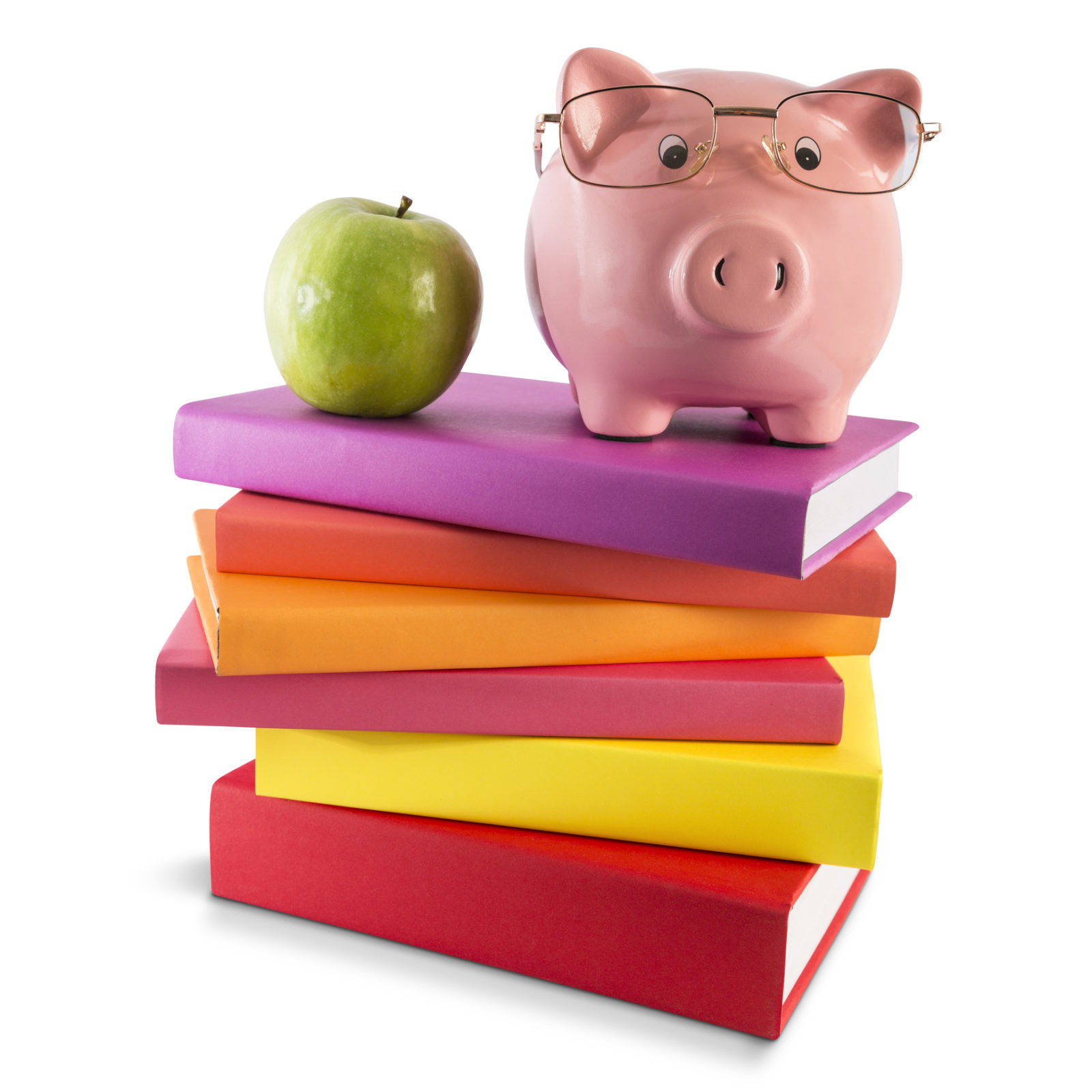 A piggy bank wearing reading glasses sits near a green apple on top of a stack of multi colored books. For educational, children and school purposes, the abstract image is isolated on a white background and contains a clipping path to easily make a selection of the image and use separately as a design element.
