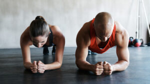 Shot of a young man and woman working out