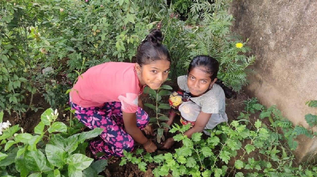 Girls planting sapling as a part of their experiential learning