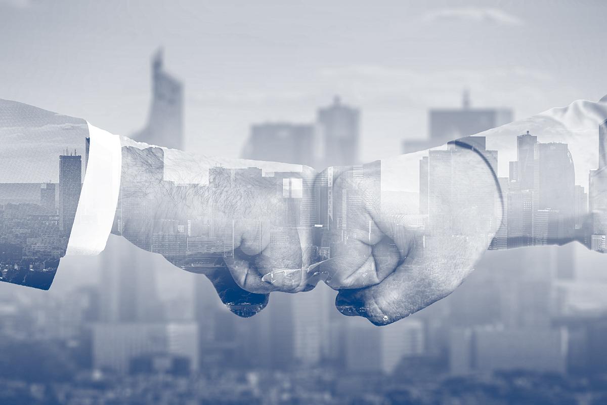 two hands fistbump against a city horizon