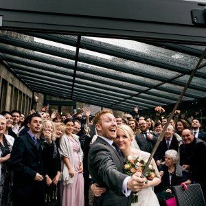 Bride and Groom do selfie with wedding guests as Rivington Hall Barn