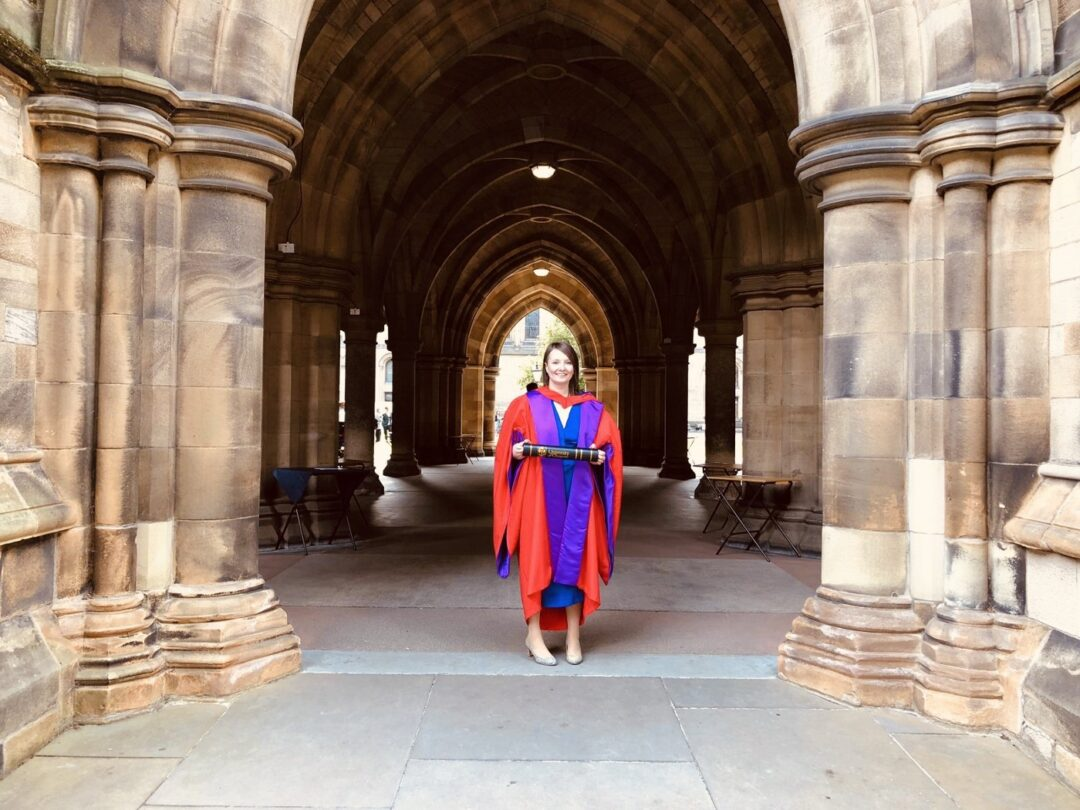 A woman standing in a purple and red gown in between an archway