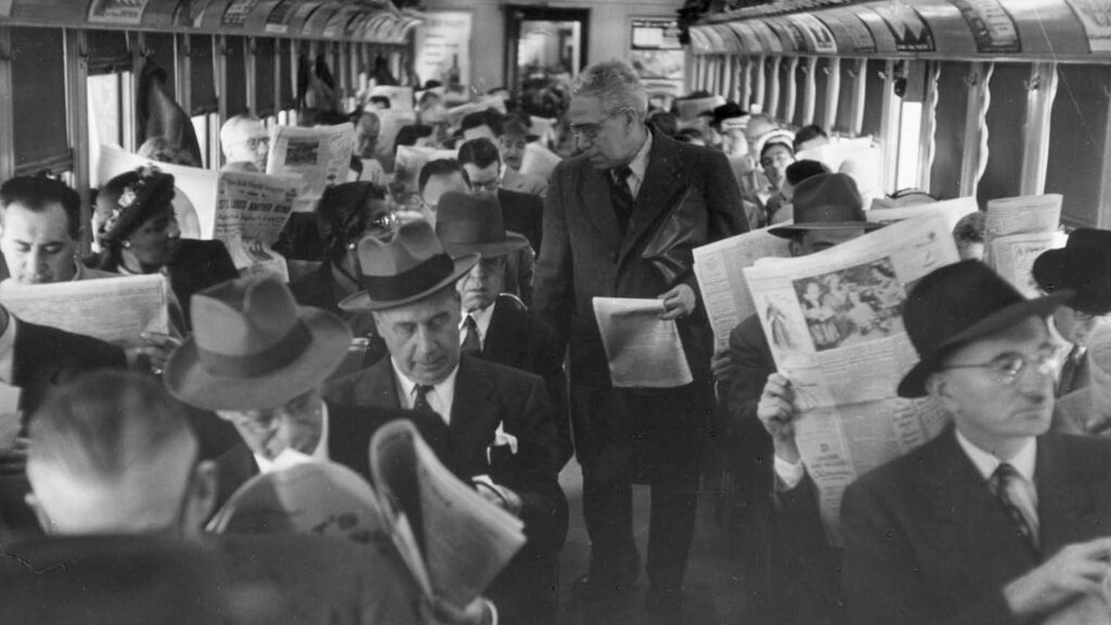 Commuters reading broadsheet newspapers on a packed train