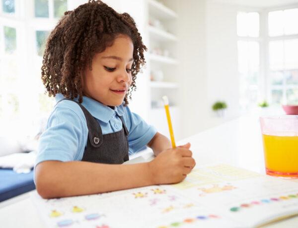 Girl In School Uniform Doing Homework In Kitchen