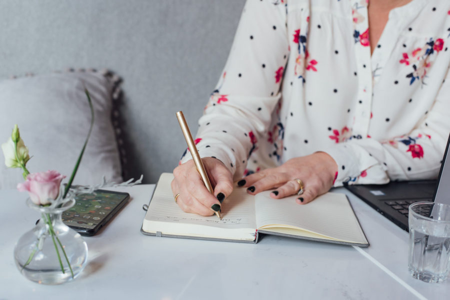 Image shows Ruth writing in a notebook with a gold pen and her phone_blog post is about content overwhelm