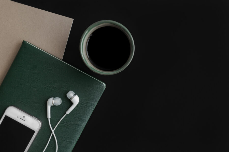Phone and headphones, coffee and two notebooks - blog post about how to create a simple content marketing plan