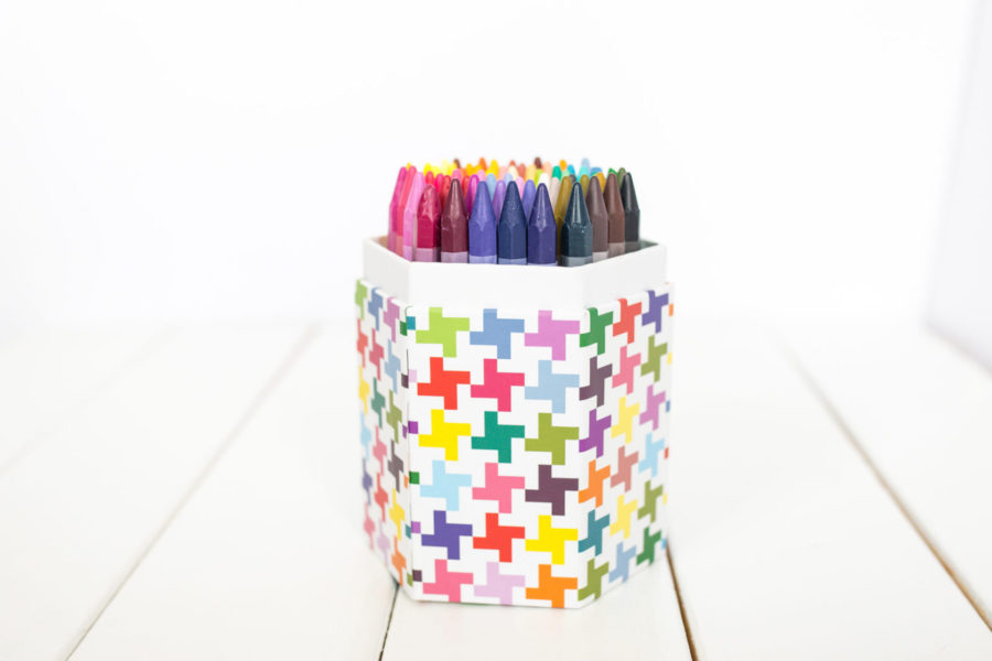 box of coloured crayons stored in a pretty container for toy rotation.