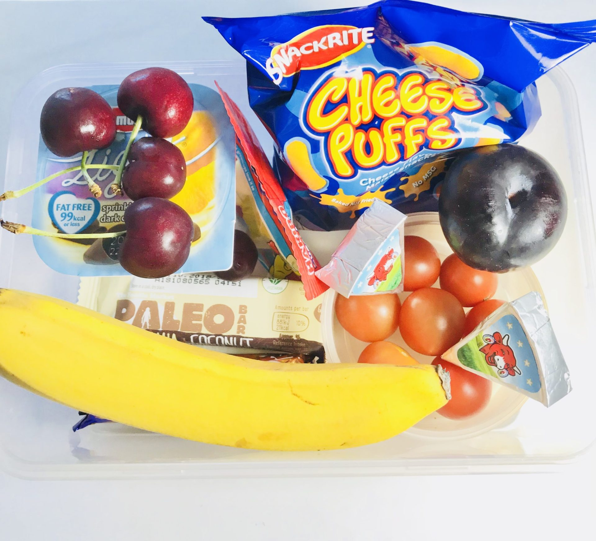 snack box idea crisps ,cherries, banana, cheese, fruit bar, cherry tomatoes yoghurt and a plum for kids snackbox