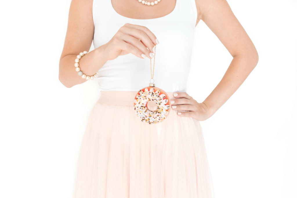 lady holding a Christmas donut bauble , how to have a debt free Christmas