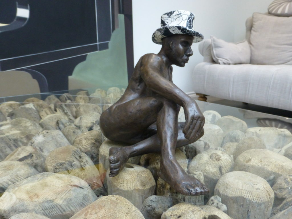 Matthew in bronze sitting on a glass coffee table