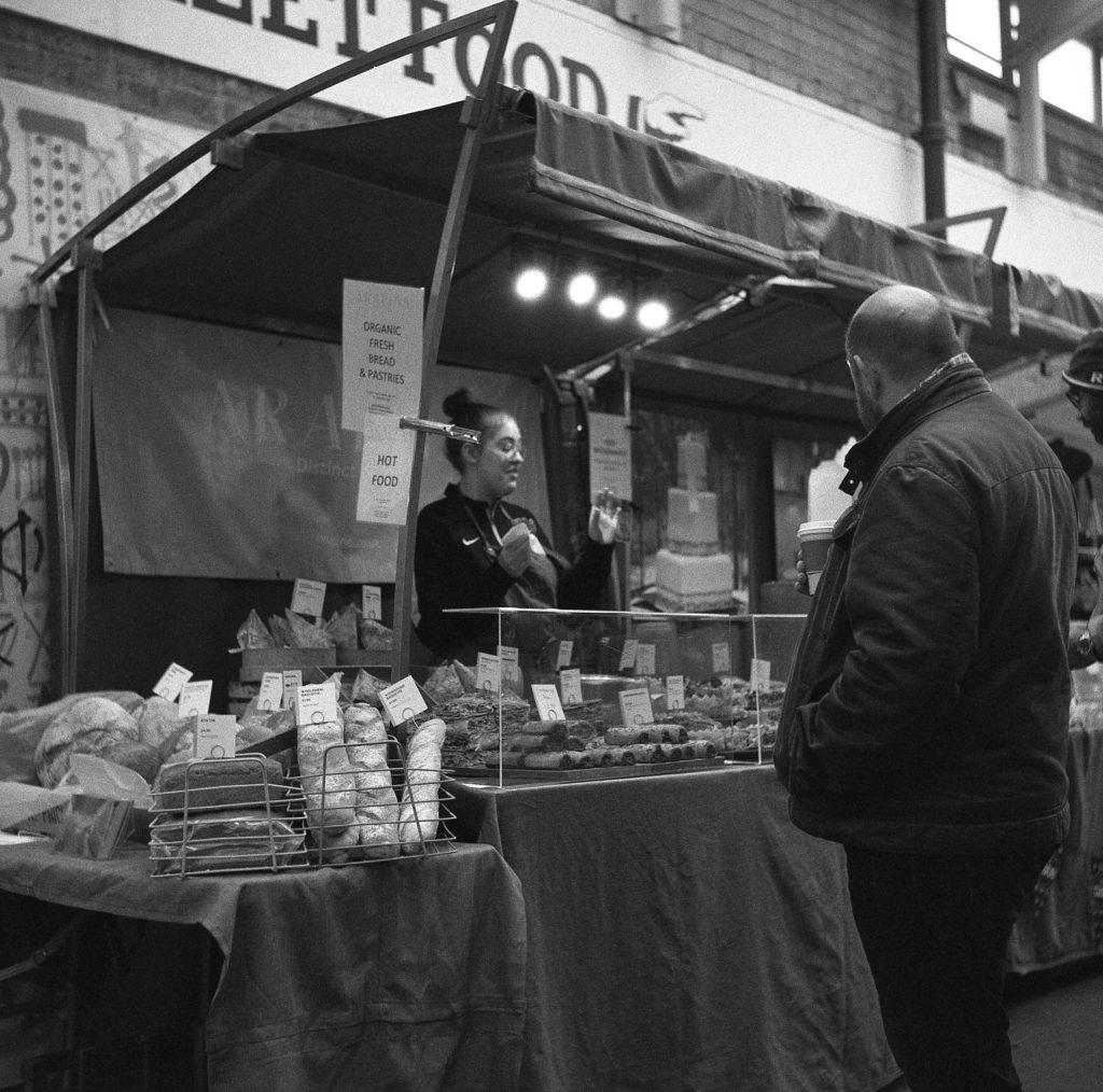 Stallholder chats to passers bye. Greenwich Market, London. Yashioca 635 TLR & Ilford Delta 400. film 120 street people b&w black white
