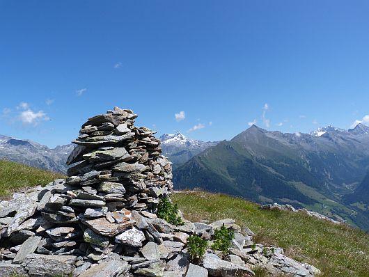Steinmanderl auf der Lassacher Höhe. Links davon schließen sich an: Ankogel, Maresenspitze, Hochalmspitze und Säuleck.
