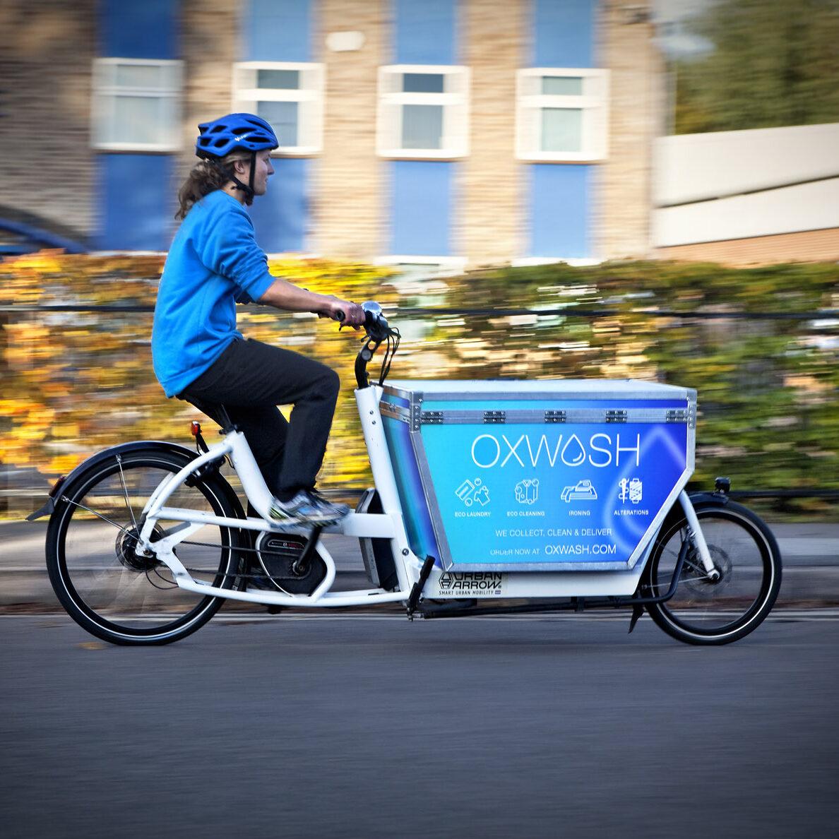 Oxwash image of rider on cargo bike delivering laundry