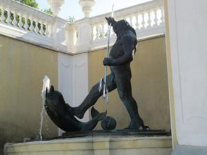 A statue of Poseidon with a dolphin