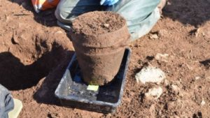 ANU Archaeologist Dr Catherine Frieman & co-director James Lewis with funerary pot in situ.